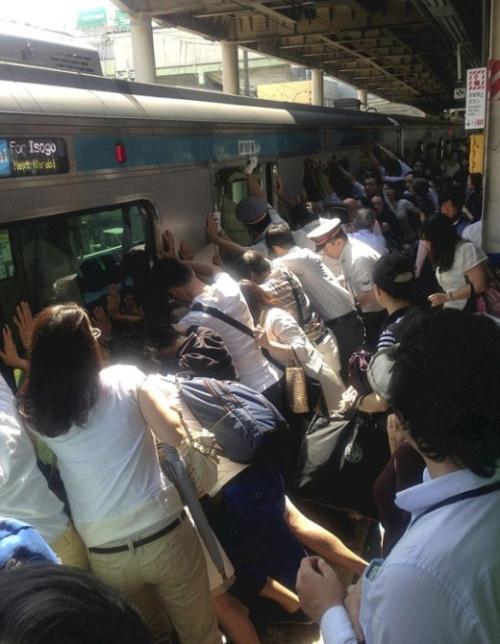 Hàng ngàn người Nhật đang cố gắng đẩy đoàn tàu nặng 32 tấn khỏi đường ray để giải cứu một người phụ nữ bị kẹt phía dưới.